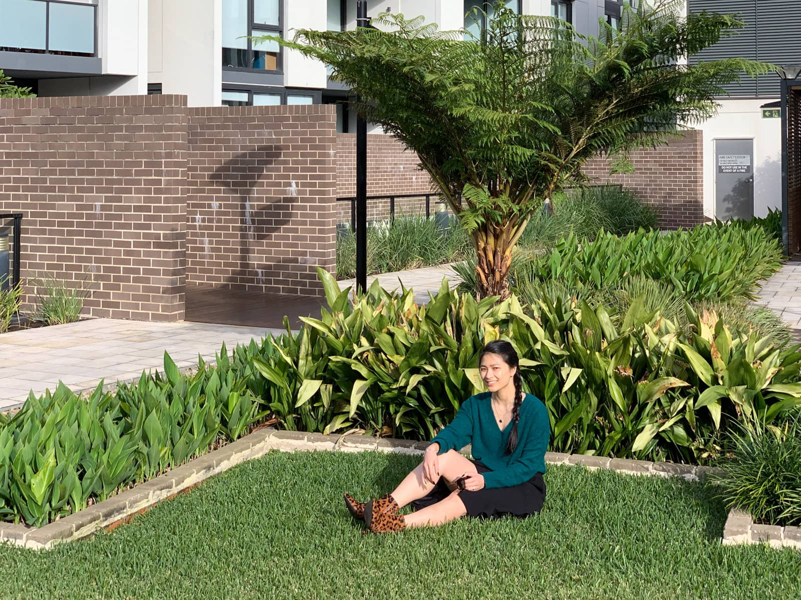The same woman in other photos on this page, sitting down in the grass of a garden. There are some plants behind her. She is sitting with legs outstretched and one knee up