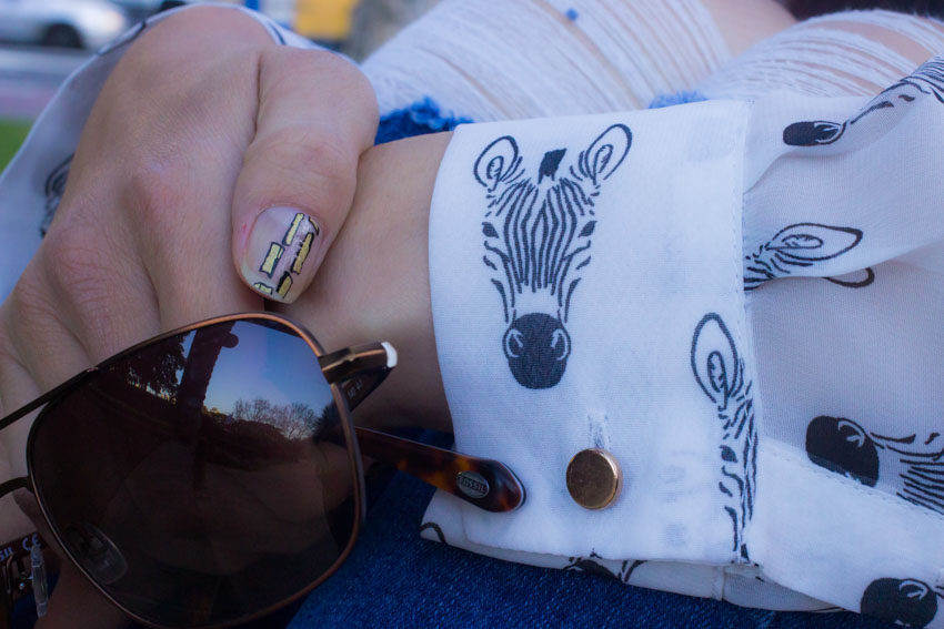 Close up of my hand, showing the print on my sleeve, my sunglasses and the nail art on my thumbnail