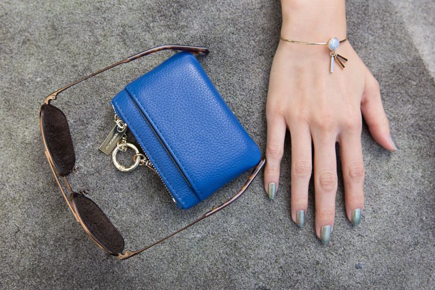 Flatlay style of my sunglasses and blue wallet with my hand in view, with my painted nails