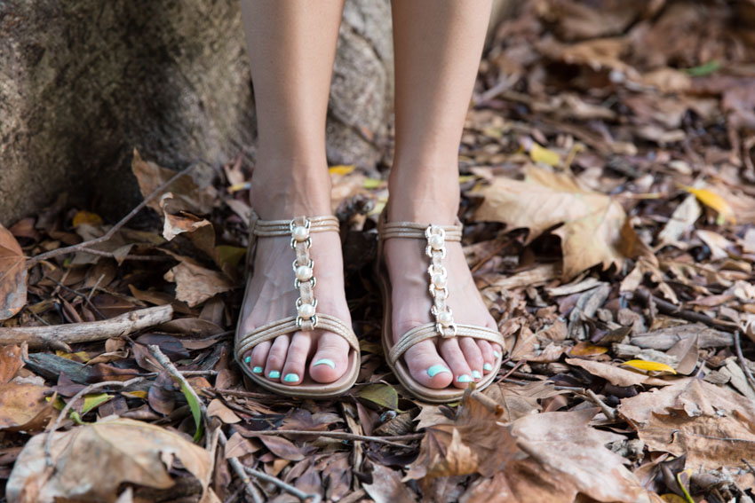 Close-up of my feet in sandals, amongst fallen leaves