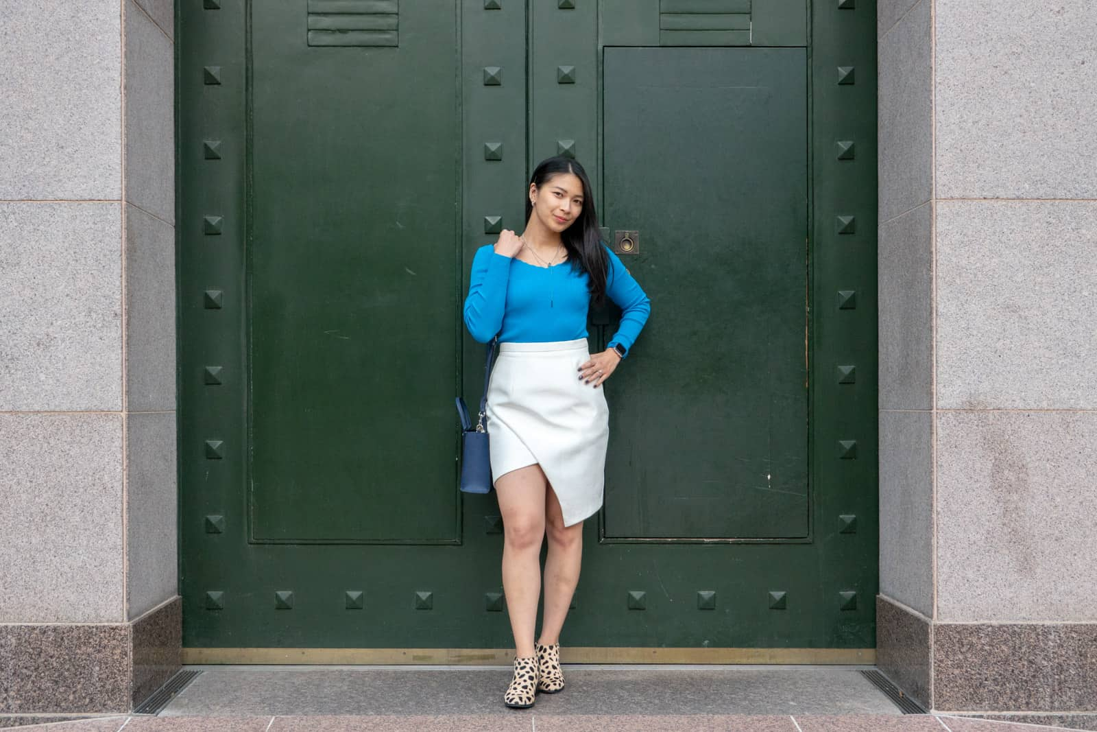 A woman standing in front of a very large dark green set of doors. She has short dark hair and is wearing a bright light blue long-sleeved top, a white wrap skirt, and shoes with animal print. She is carrying a small navy handbag on her shoulder and has a hand on her hip.