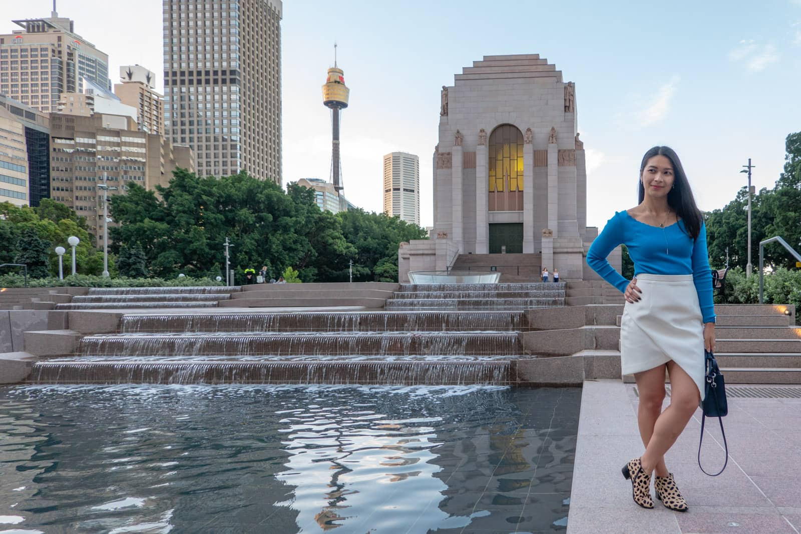 The same woman in other photos on this page, in the same outfit. She is standing by a reflecting pool with a water feature where the water flows down some steps. The city can be seen in the background.