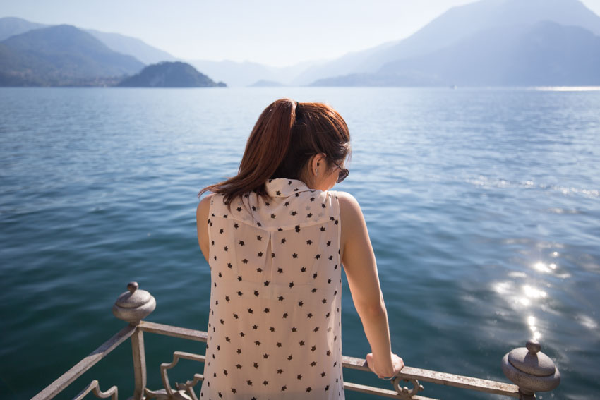 Me leaning on a small balcony railing looking out on Lake Como