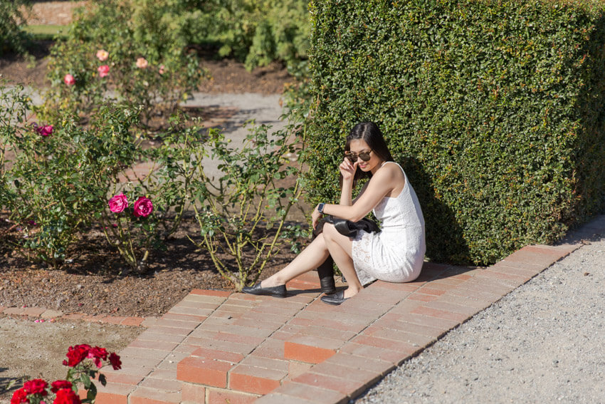 A woman with short dark hair and sunglasses, in a sleeveless white dress sitting on a step in a rose garden. She has a black jacket on her lap and is holding the frame of her glasses with one hand.
