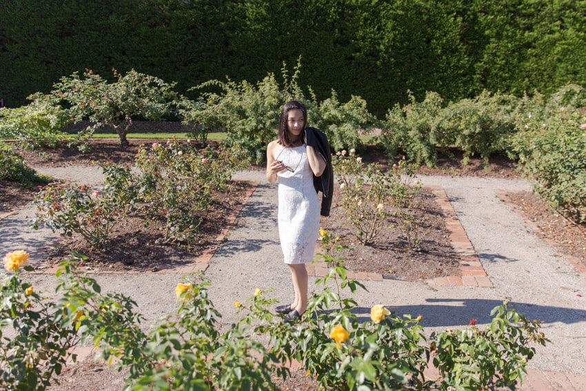 A woman in a strapless white dress standing in the dirt paths of a rose garden. There are small garden inlays in the dirt paths. The woman is holding her sunglasses between her fingers and with the other hand has a leather jacket slung over her shoulder