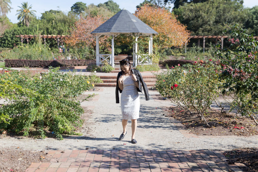 A woman in a white dress with a black jacket draped over her shoulders, looking down, mid-step. She is wearing black loafers and in the background is a gazebo and a rose garden.