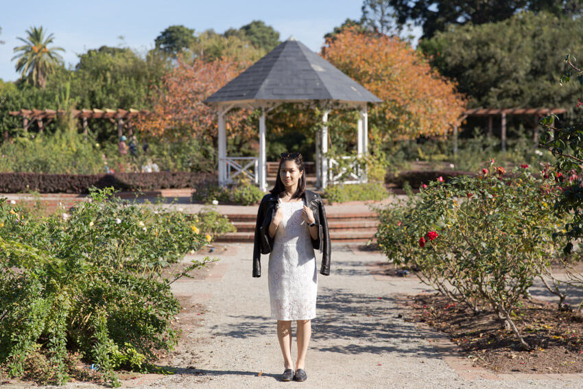 A woman in a white dress with a black jacket over her shoulders, facing the camera. In the background is a gazebo and a rose garden.