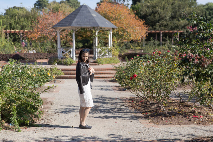 Side view of a woman wearing a white lace dress with a black leather jacket draped over her shoulders. She is standing in a rose garden with a dirt path and in the background is a gazebo.