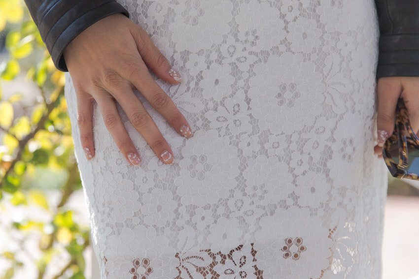 A close, front-on shot of a woman's hand against the white lace dress she is wearing. Her fingnernails have a white floral design that still shows the bare nail where the design is not printed.