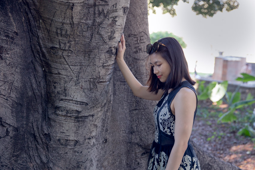 A woman with sunglasses on top of her head, standing by a large tree trunk. She has her right hand resting on the tree. She is wearing a sleeveless black dress with gold embroidery.
