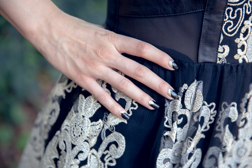 A close-up of a woman's right hand on her hip. She has black nails with gold glitter chevron accents. The dress she is wearing is made of black mesh and gold embroidery.