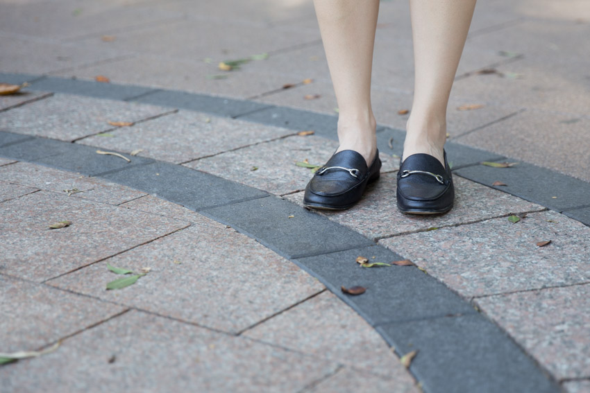 A woman's feet with black loafers, standing on black and light brown tiled pavement with the tiles laid out in concentric circles. Some leaves sit on the pavement.