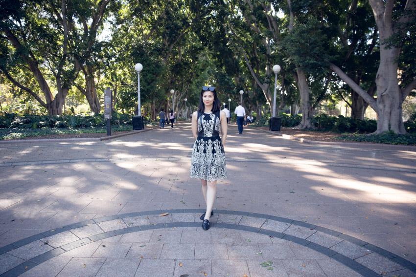 A woman wearing a black and gold sleeveless, knee-length dress. She has short dark hair and is wearing sunglasses on top of her head. She has her hands behind her back and is wearing black loafers. She is standing at the entrance to a park with a wide path extending behind her, lampposts on the edges of the wide paths and many tall trees in the background