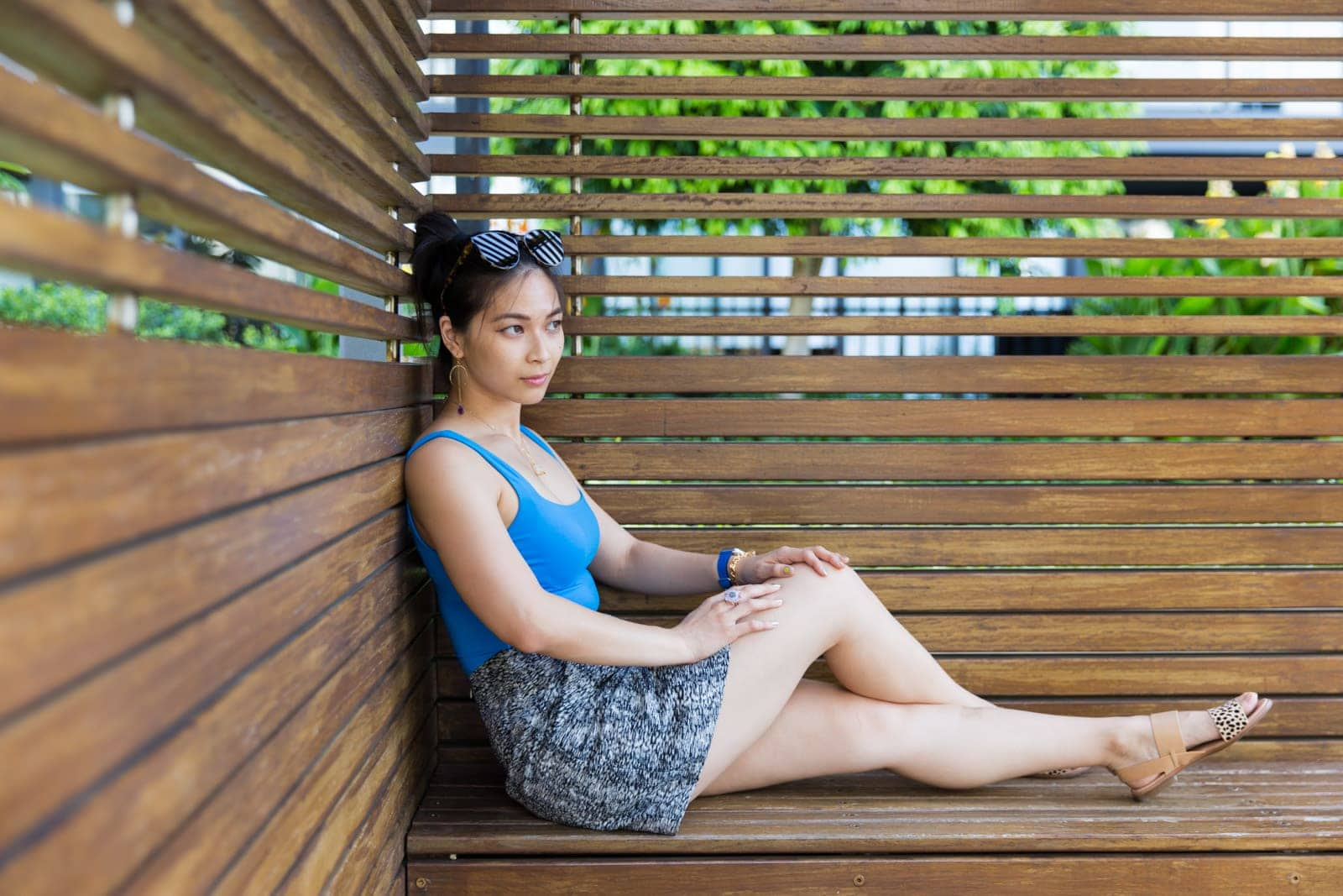 A woman with dark hair in a bun, wearing a blue bodysuit and a black and white textured skirt. She is sitting on a wooden bench in a cabana, with her legs outstretched and ankles crossed. She is wearing nude coloured sandals with a spotted strap over the toes