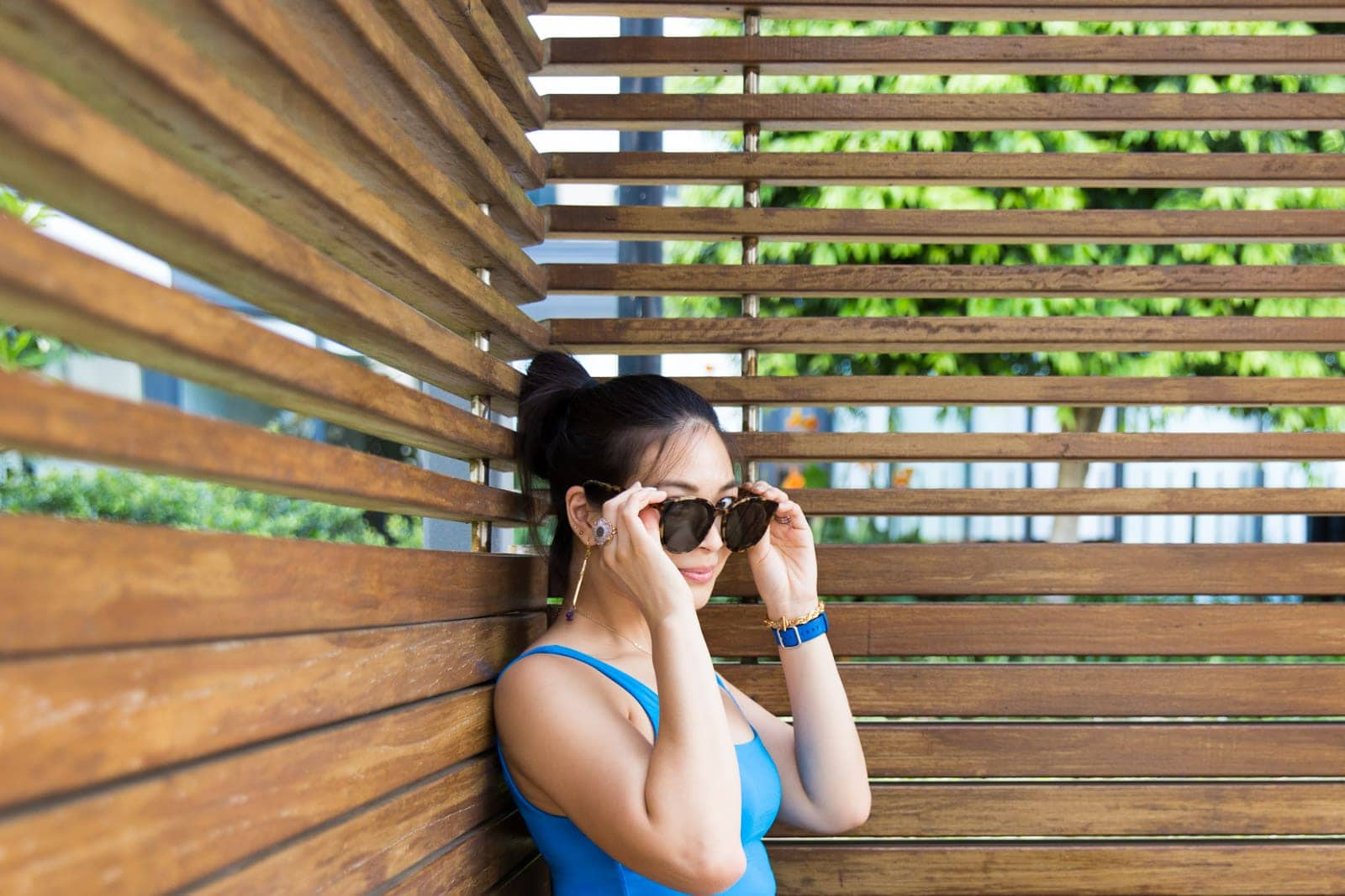 A woman with dark hair in a bun, wearing a blue top. She is holding her round sunglasses to her face, almost covering her eyes. Her eyes are wide open