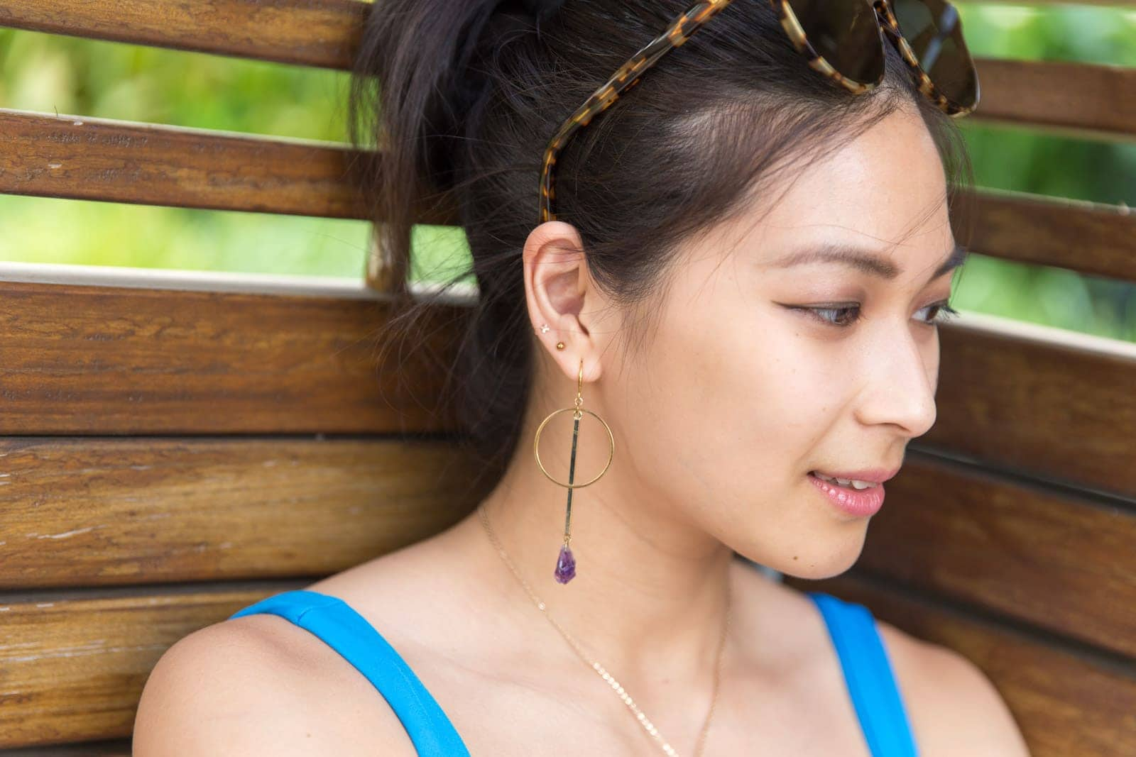 A closeup of a woman's face, her face angled slightly away from the camera. She has gold hoop earrings in her ear with a raw amethyst crystal drop