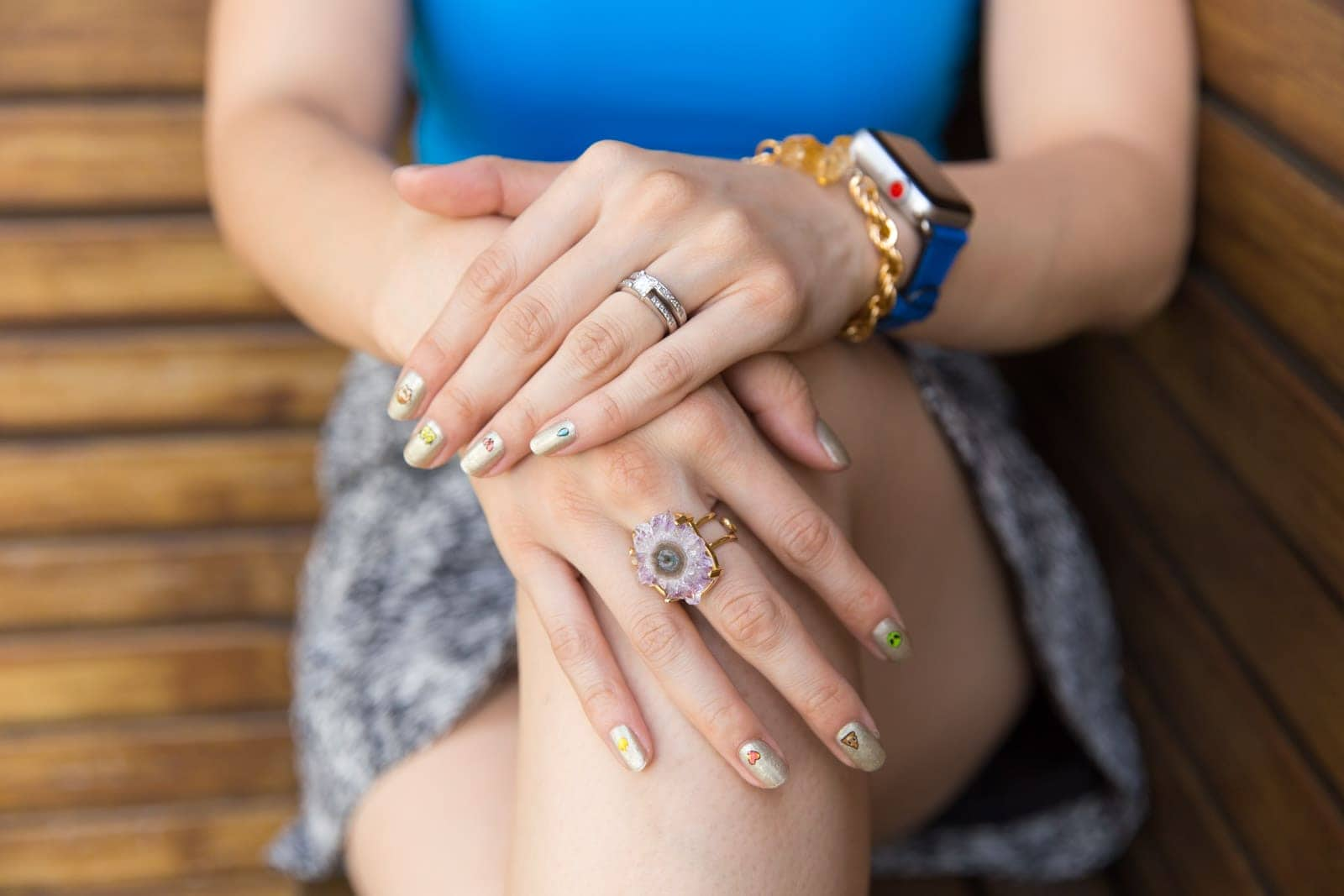 A close up of a woman's hands on top of each other, resting on her bent knee. She has a large purple amethyst ring on one hand, and a white gold engagement ring and wedding ring on the other. Her nails are a gold glitter colour with a small cartoon image on each nail.