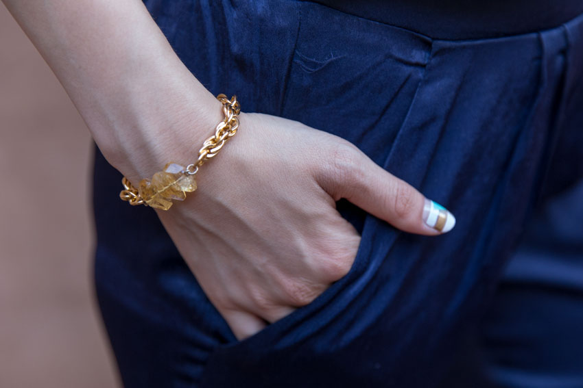 Close up of gold chain bracelet with yellow crystals, with my hand in my pocket