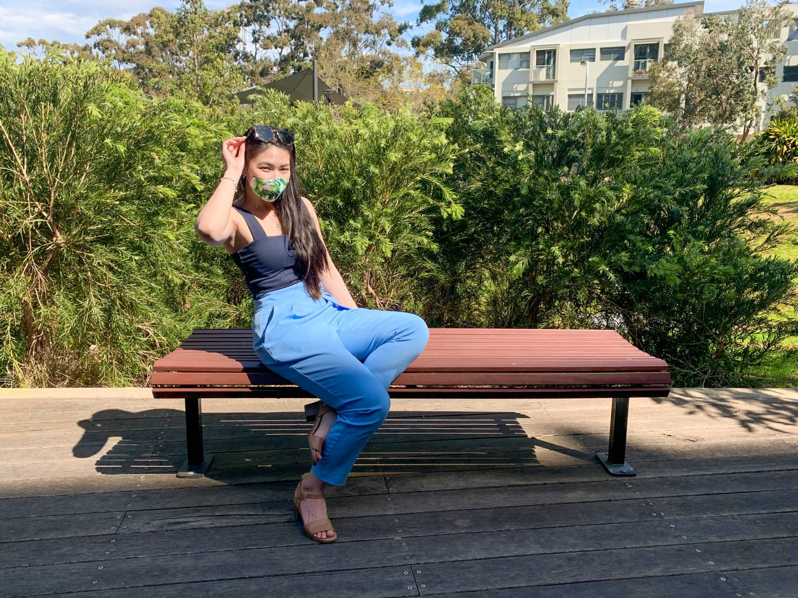 The same woman in other photos on this page, wearing the same clothes. She is sitting on a wooden bench, leaning back a little, with her ankles crossed at the ground beneath the bench. She is holding onto her sunglasses on top of her head