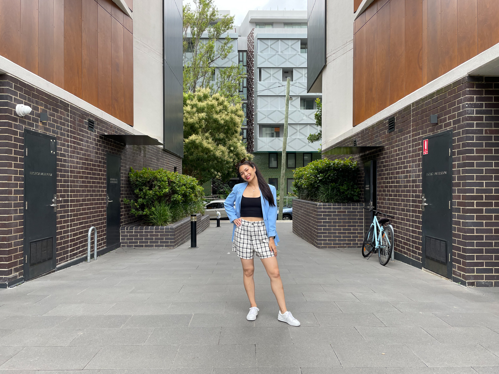 The same woman from previous photos on this page, wearing the same outfit. She is standing in a walkway with brick walls with storeroom doors on either side. There is a street and apartment building in the background behind her. She has one hand on her hip.