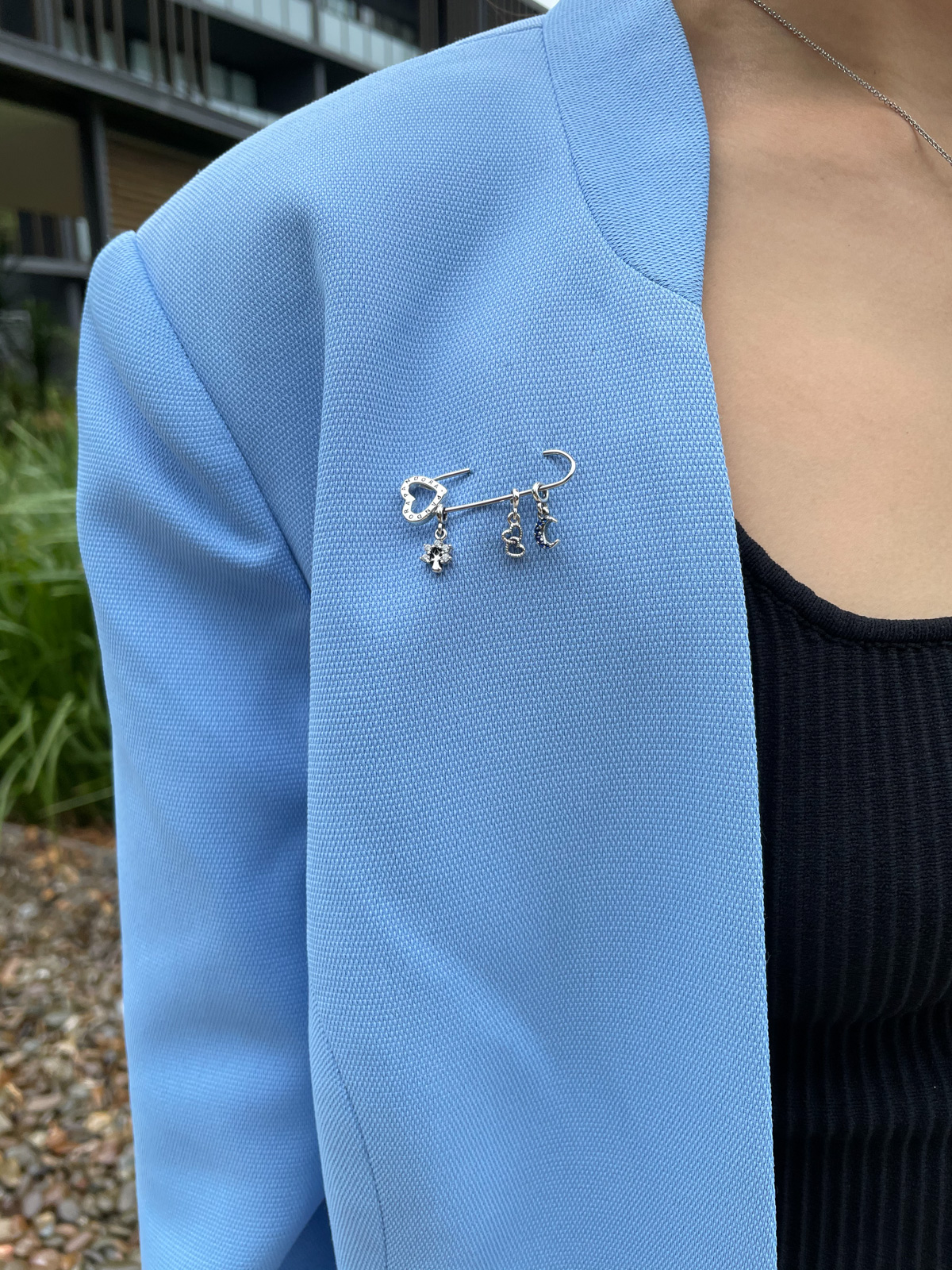 A close-up of the lapel of a woman's blue blazer. It has an adorned safety pin with three charms pinned on it: a tree; two hearts; and a moon. The tree and moon are adorned with rhinestones