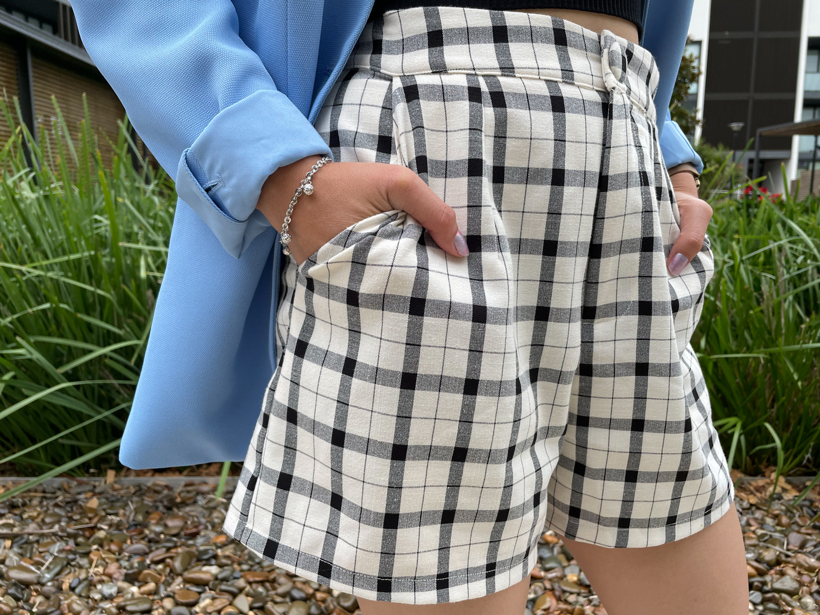 A close-up of a woman wearing shorts with a plaid print. She has her hands in the pockets.
