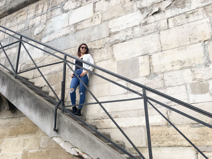 Me leaning on a wall with a set of stairs, by the Seine River