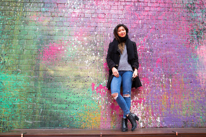 Me standing in front of a bright colourfully painted wall