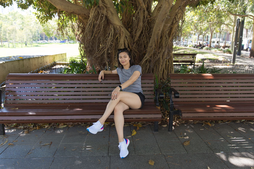 Me sitting on a brown wooden bench, with my left leg crossed over my right. My left hand rests on my left knee and my right arm is draped over the back of the bench. I am looking somewhere beyond the camera.