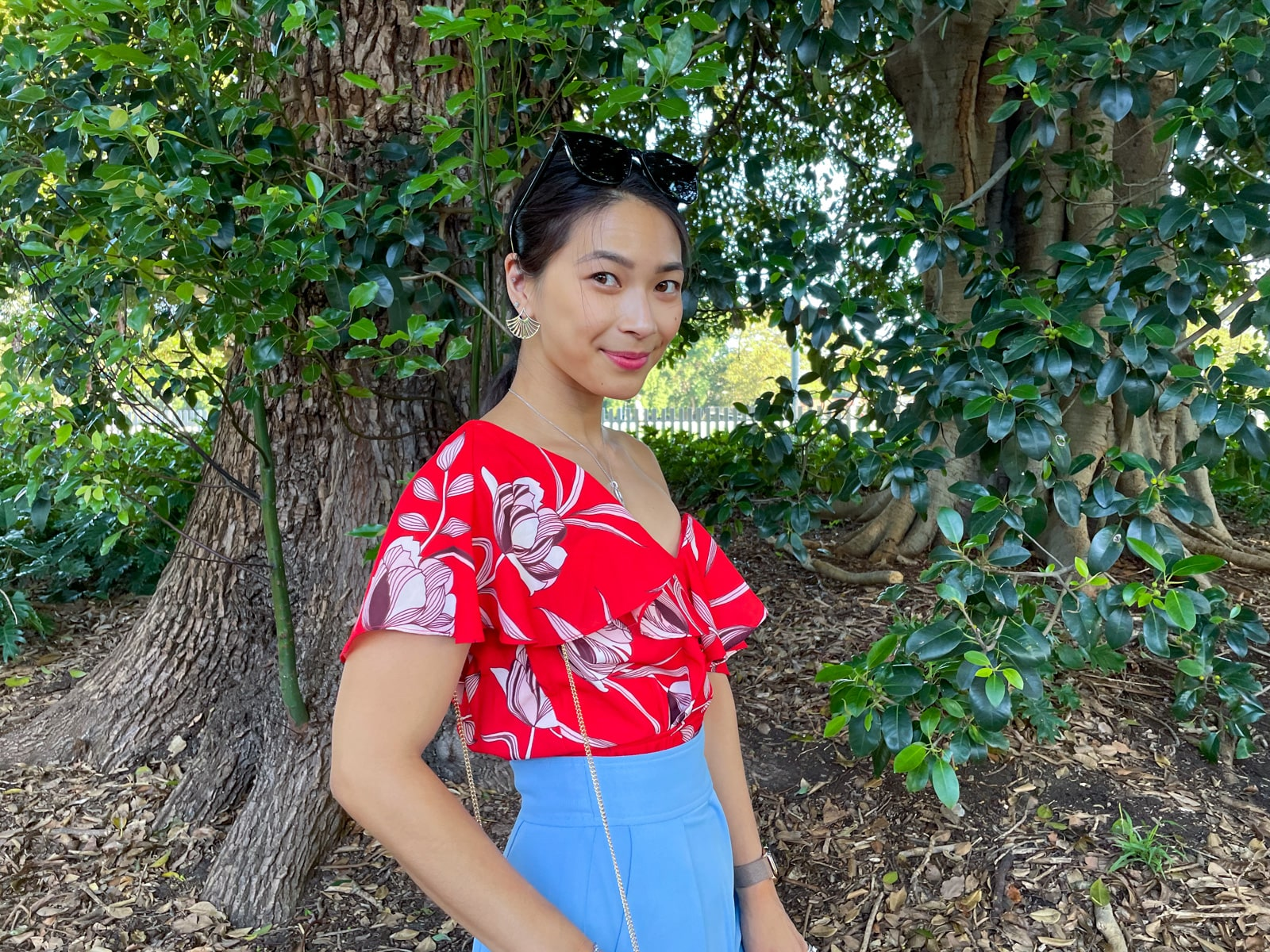 An Asian woman wearing a red top with a floral print, and blue pants, with her hair tied back in a low ponytail. She has black sunglasses on top of her head and is smiling with her chin pointed downwards as she looks up. She is standing in front of a tree.