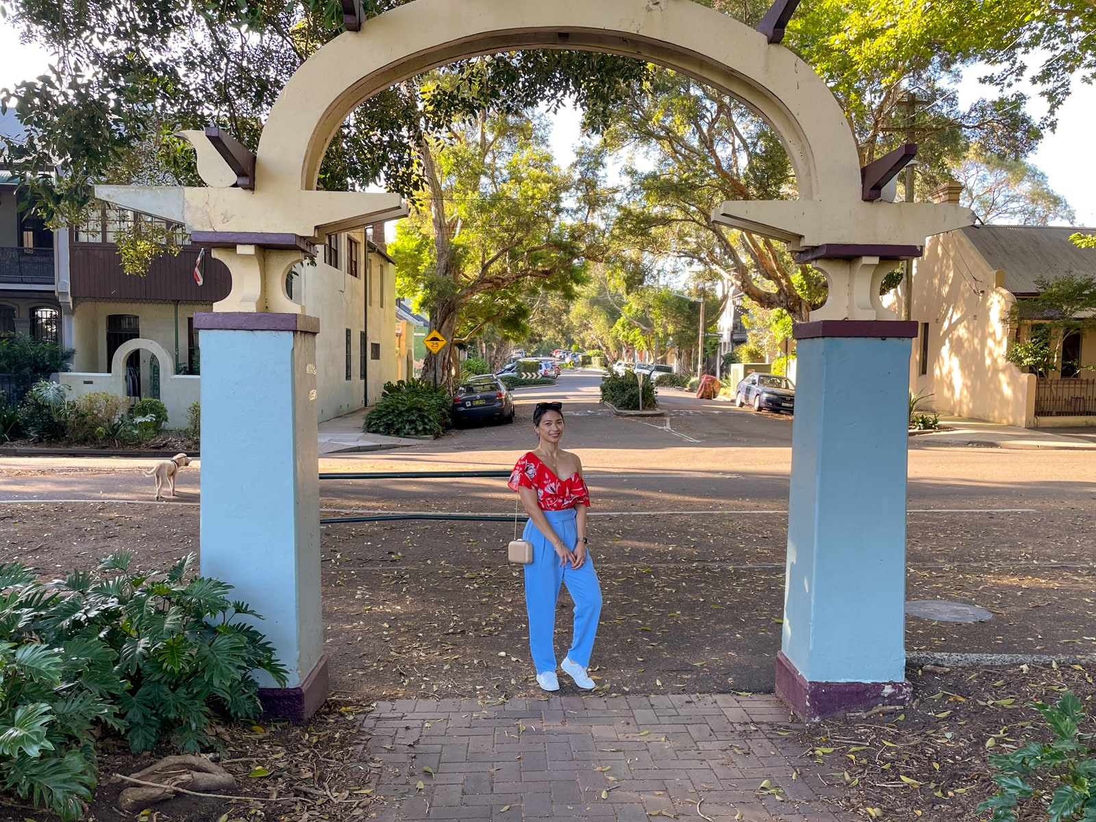 An Asian woman wearing a red top with a floral print, and blue pants, with her hair tied back in a low ponytail. She has white shoes on. One of her knees is bent and her hands are clasped together. She's standing under a concrete arch that marks the entrance to a park. Behind her is a suburban street.