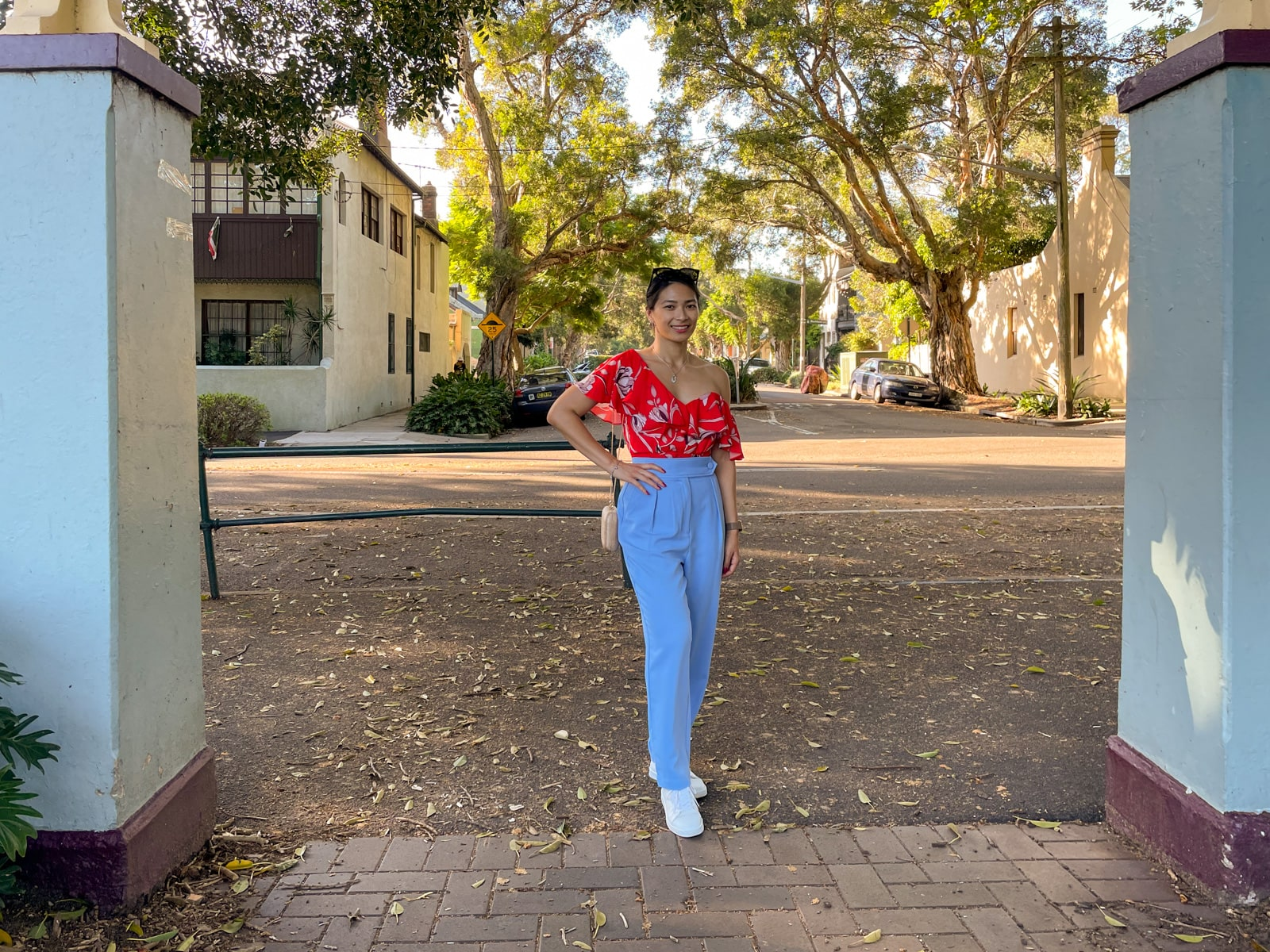An Asian woman wearing a red top with a floral print, and blue pants, with her hair tied back in a low ponytail. She has a hand on her hip, showing a gold coloured rounded rectangular clutch bag hanging from a chain on her shoulder. She is standing under a concrete arch at a park.