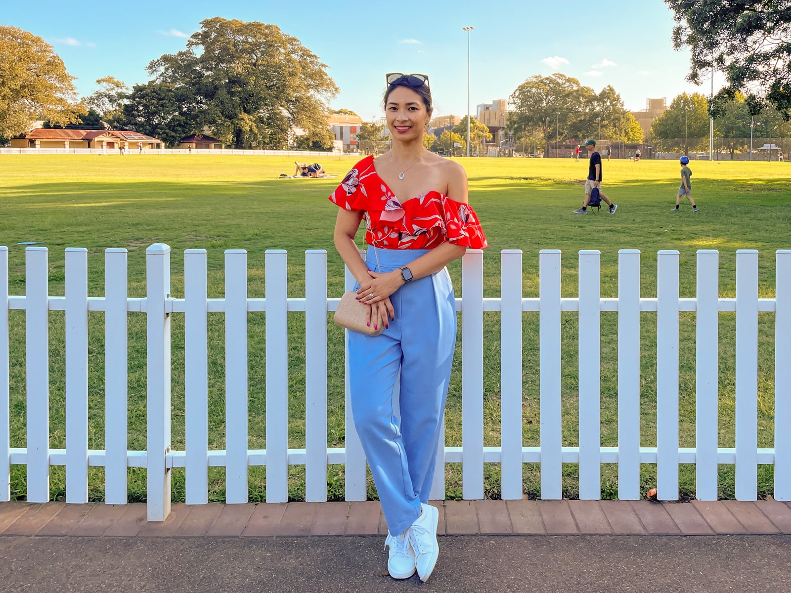 An Asian woman wearing a red top with a floral print, and blue pants, with her hair tied back in a low ponytail. She has black sunglasses on top of her head and is wearing white shoes. She holds onto a gold clutch bag hanging from her shoulder. She stands in front of a white fence along a sports oval.