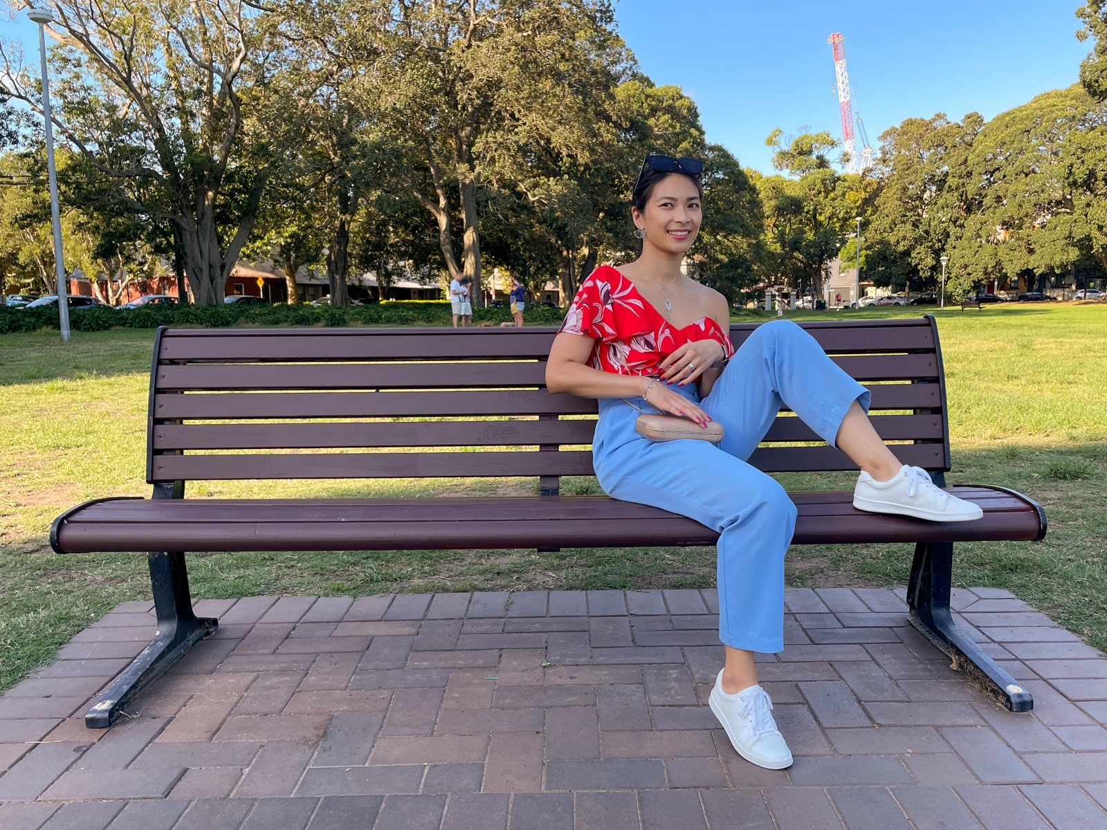 An Asian woman wearing a red top with a floral print, and blue pants, with her hair tied back in a low ponytail. She has white sneakers on and is sitting on a bench, with a leg bent and her foot up on the bench.