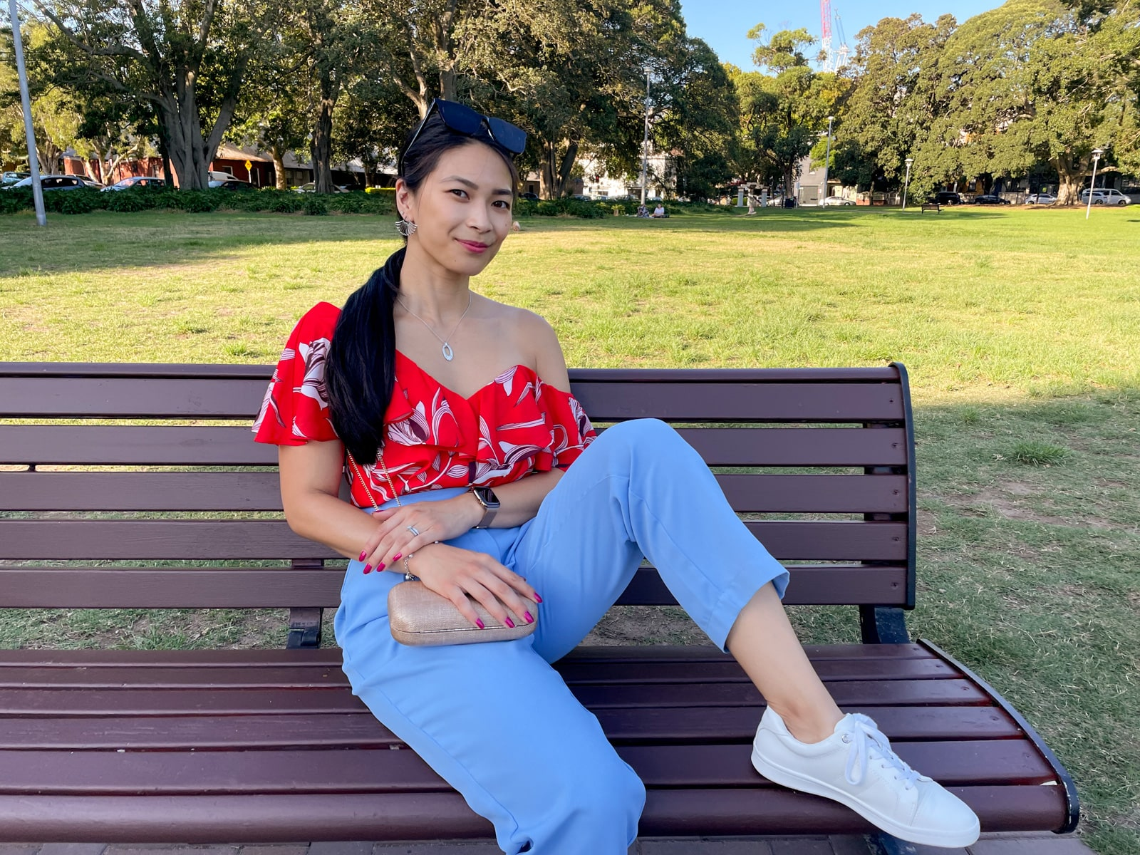 An Asian woman wearing a red top with a floral print, and blue pants, with her hair tied back in a low ponytail. She is leaning back on a bench with a gold clutch handbag in her lap. She has a foot up on the bench with her knee bent.