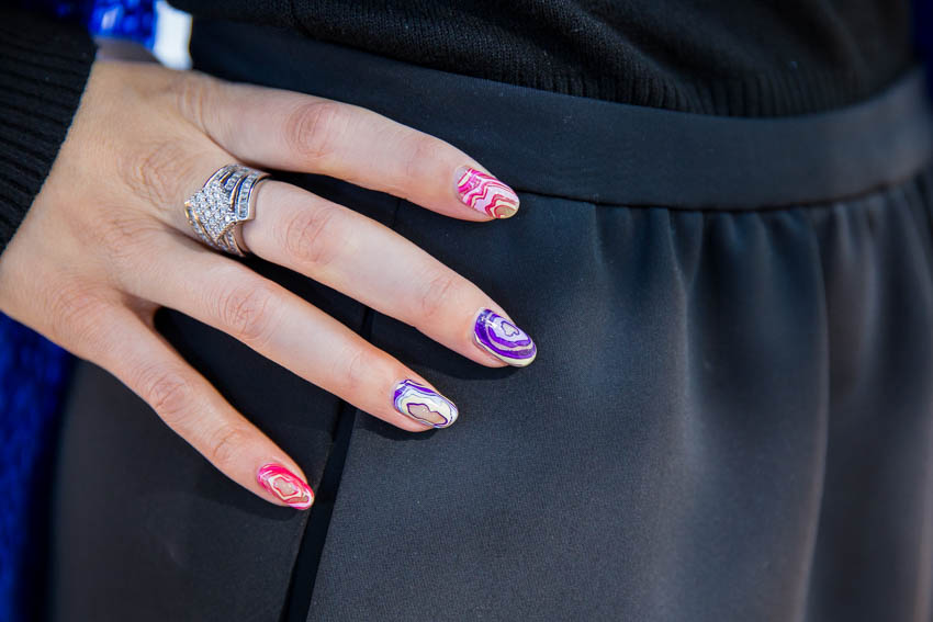 My right hand at my hip, showing a statement ring and geode-style nails