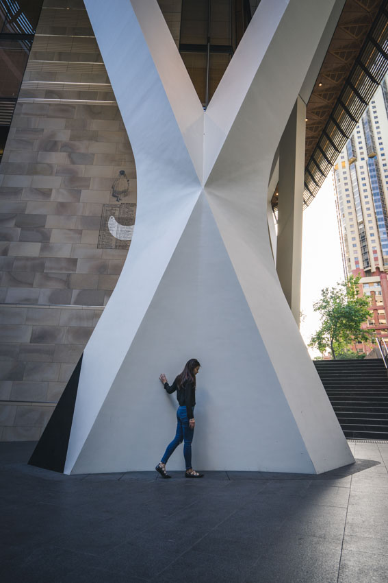 Walking in front of an interesting X-shaped white pillar