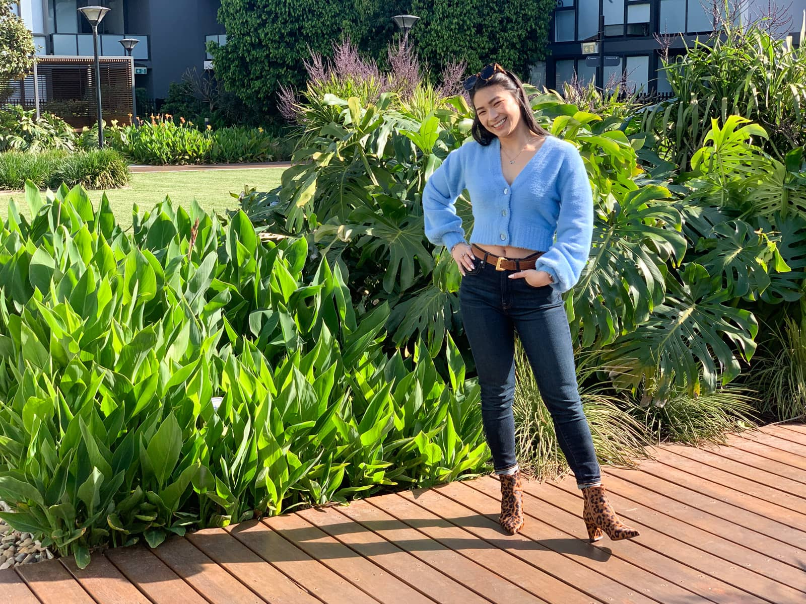 The same woman in the previous photo on this page, in the same outfit. She is standing on a wooden boardwalk with a hand on her hip and another in her jeans pocket. Behind her are some large green plants.