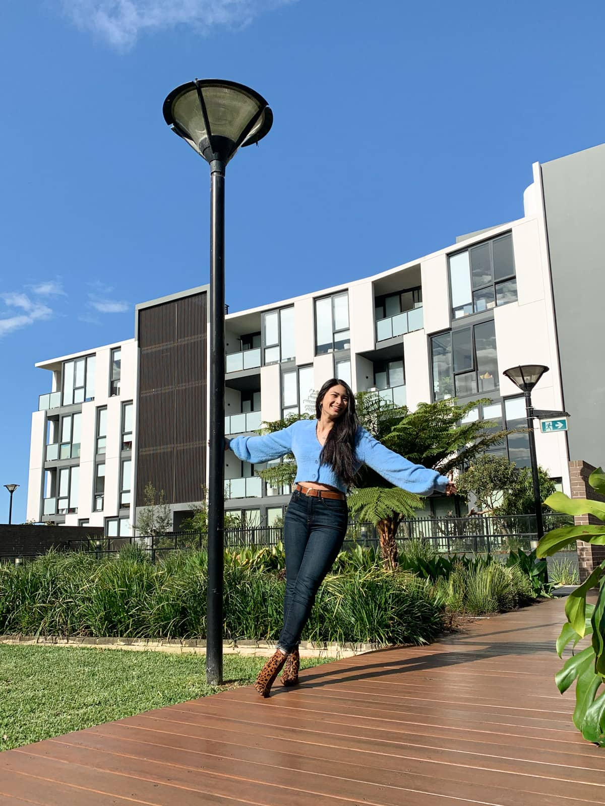 The same woman in the other photos on this page, in the same outfit. She is holding onto a lamppost and stretching out to the opposite side, with her ankles crossed. She is standing on a wooden boardwalk. In the background is an apartment building and the sky is blue like her cardigan.