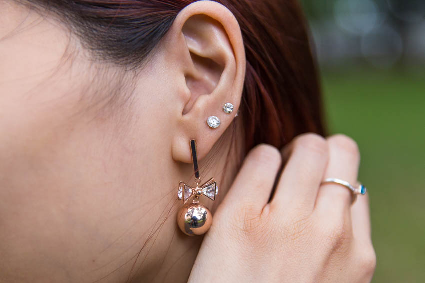 Close up of rose gold ball and bow earrings