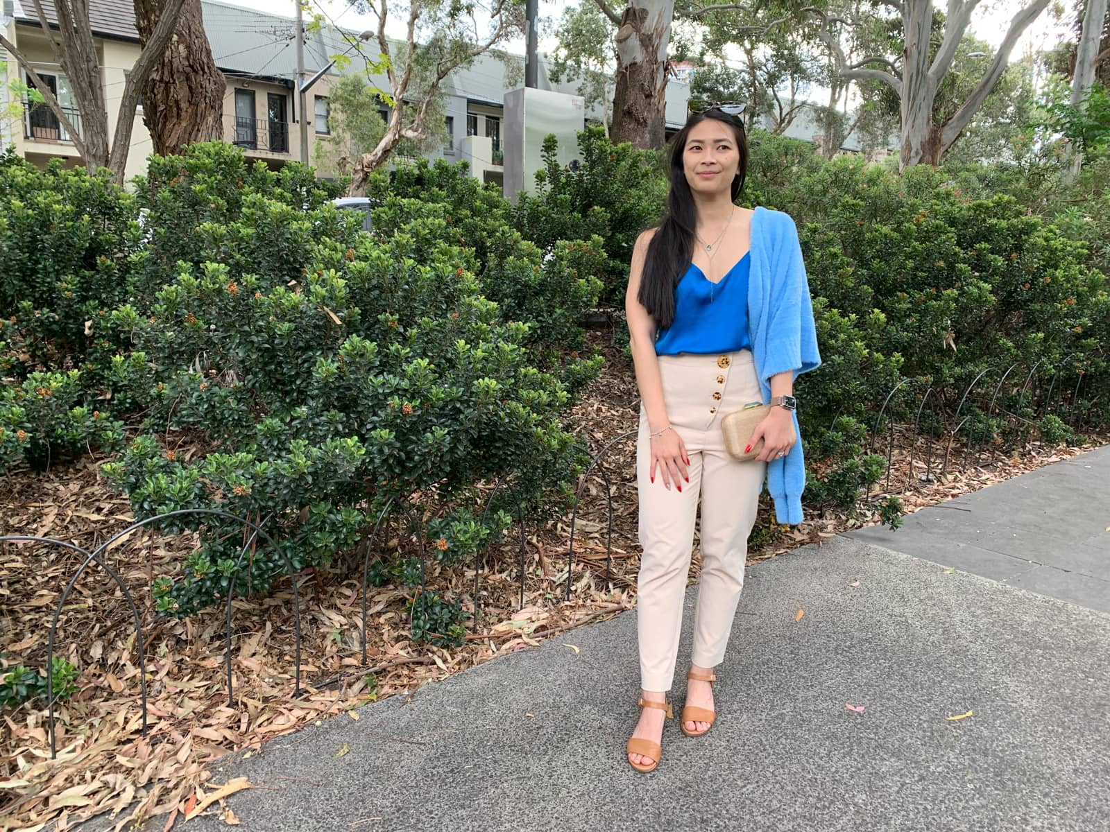 The same woman in the previous photos on this page, in the same outfit. She is standing in front of shrubbery and has one hand clutching her handbag and the other resting on her upper thigh
