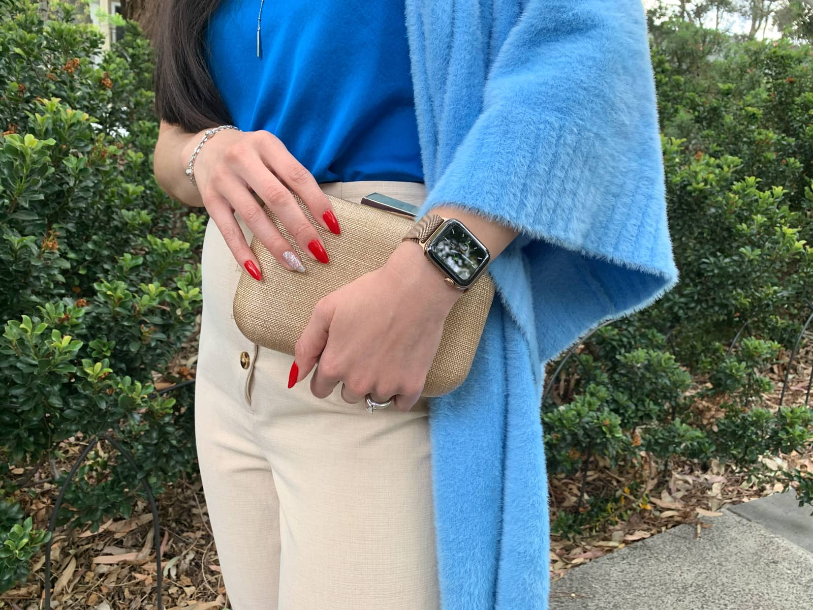 A close-up of a woman's red manicured long nails clutching a small rounded rectangular clutch handbag. Her sky blue cardigan can be seen and she is wearing a bright blue top and light pants