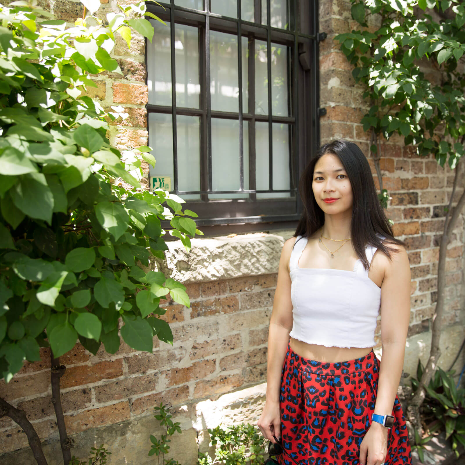 The same woman from other images on this page, in the same outfit. She is standing by a closed window in the brick wall of a building. There are some growing vines on the wall.
