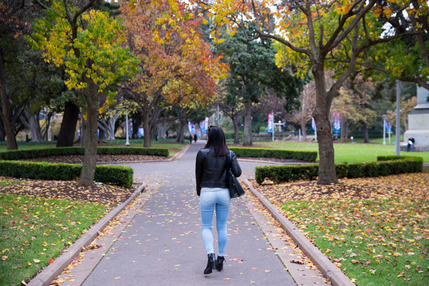 A view from the back of a woman walking down a path with autumn trees in the background.