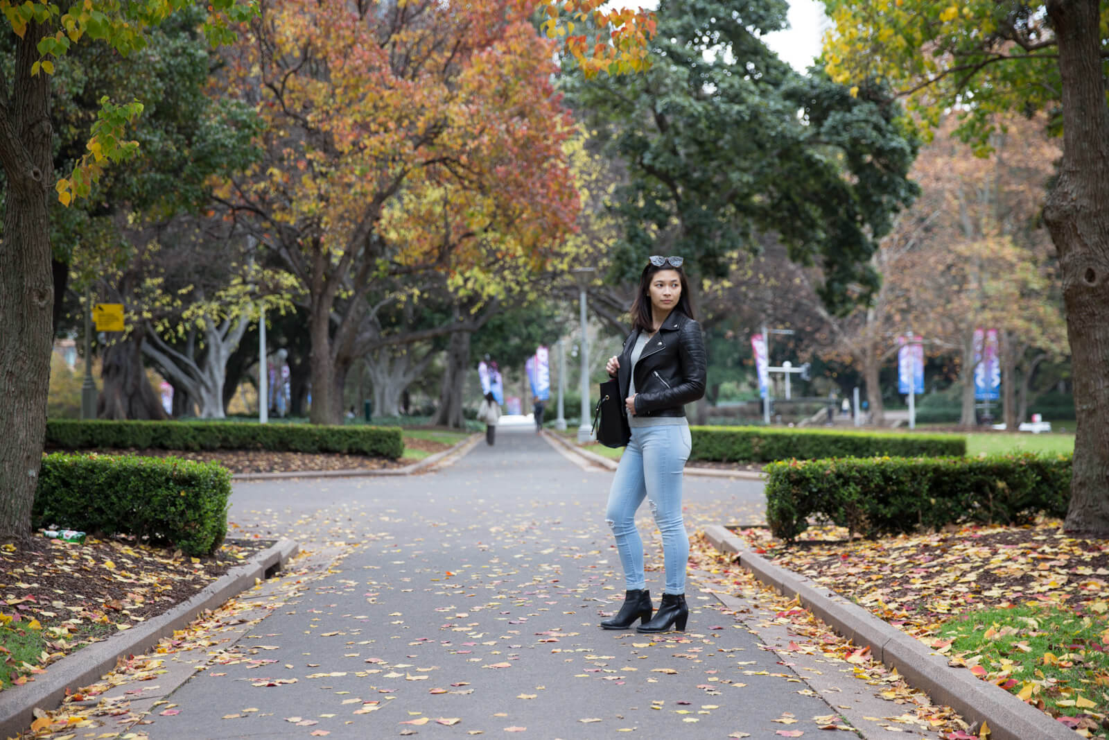 A woman in light blue jeans and a black leather jacket, holding a handbag over her right shoulder. Her left side faces the camera. She is standing on a path surrounded by trees with yellow and green leaves.