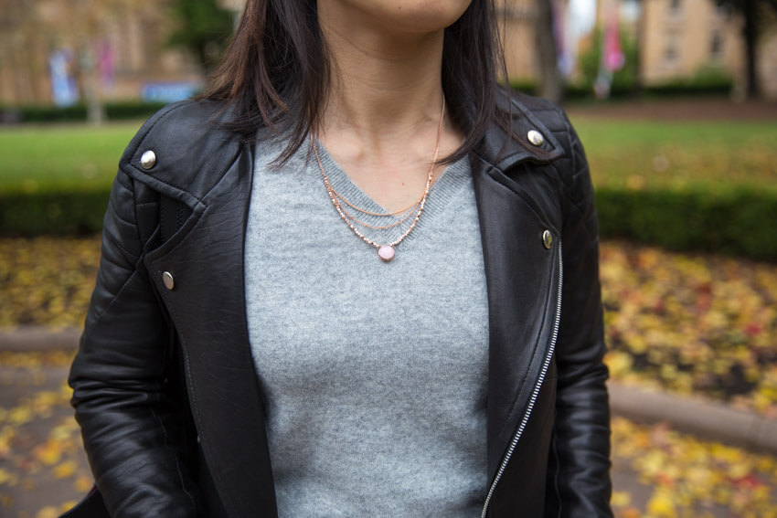 A close shot of a woman in a grey v-neck sweater wearing a rose gold necklace with layered chains and small beads, and a pink-coloured pendant drop