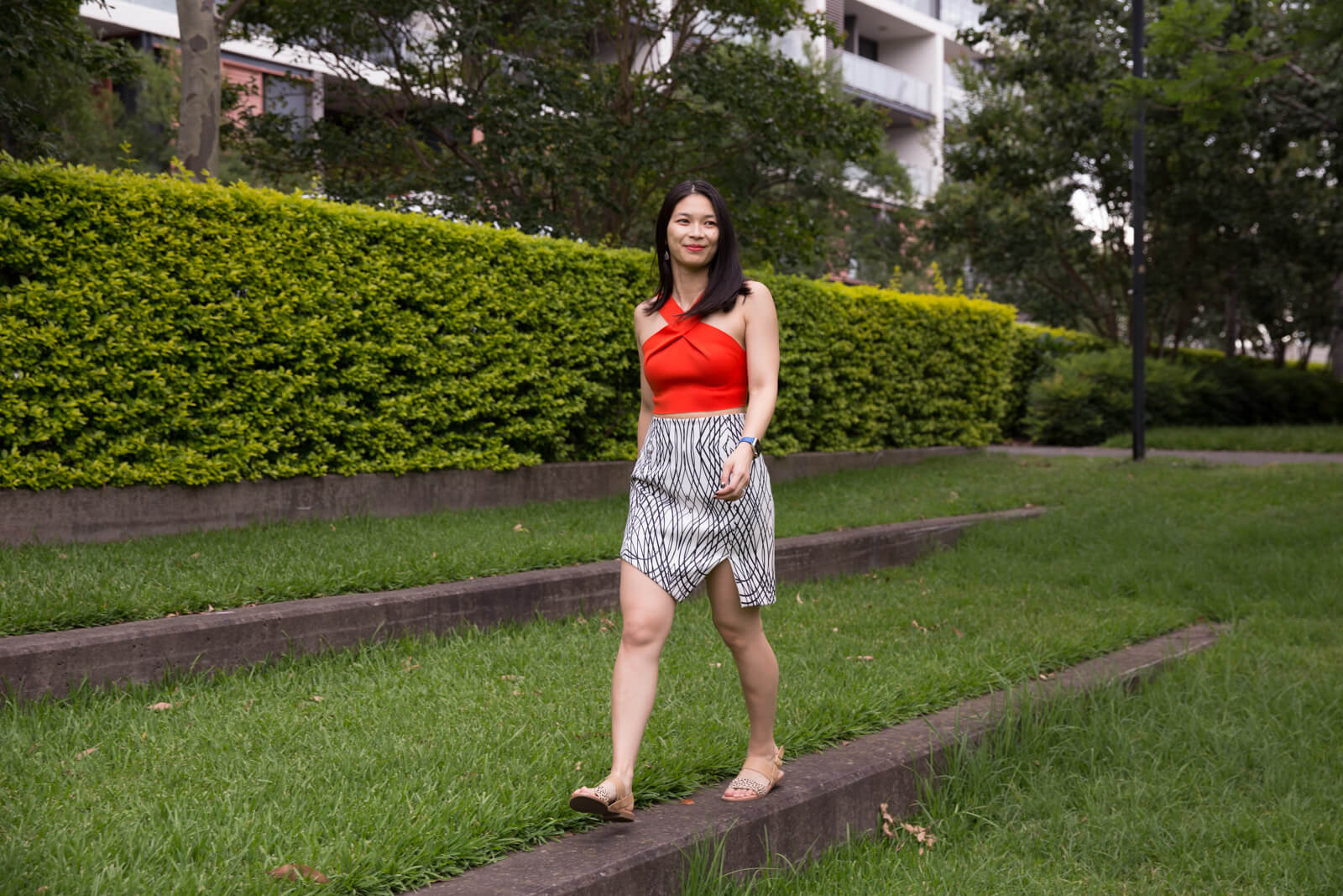 A full body shot of the same woman from other photos in this post, in the same outfit, walking across a concrete step lined with grass.
