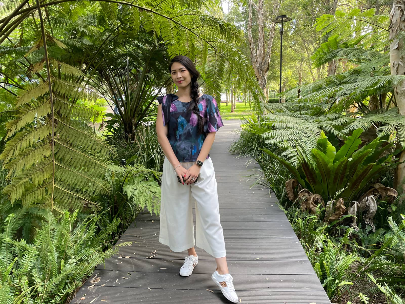A woman with fair skin and long dark hair braided loosely in a side braid. She is wearing a patterned top and white culottes, and standing on a boardwalk surrounded by fern-like trees.