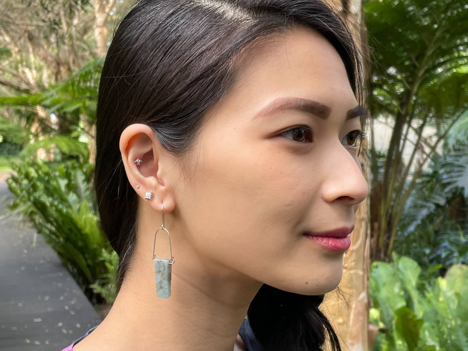 A close-up of a woman's face from the side. She has silver earrings in her ear, with the bottommost earring being a silver wire earring with a raw aquamarine stone drop