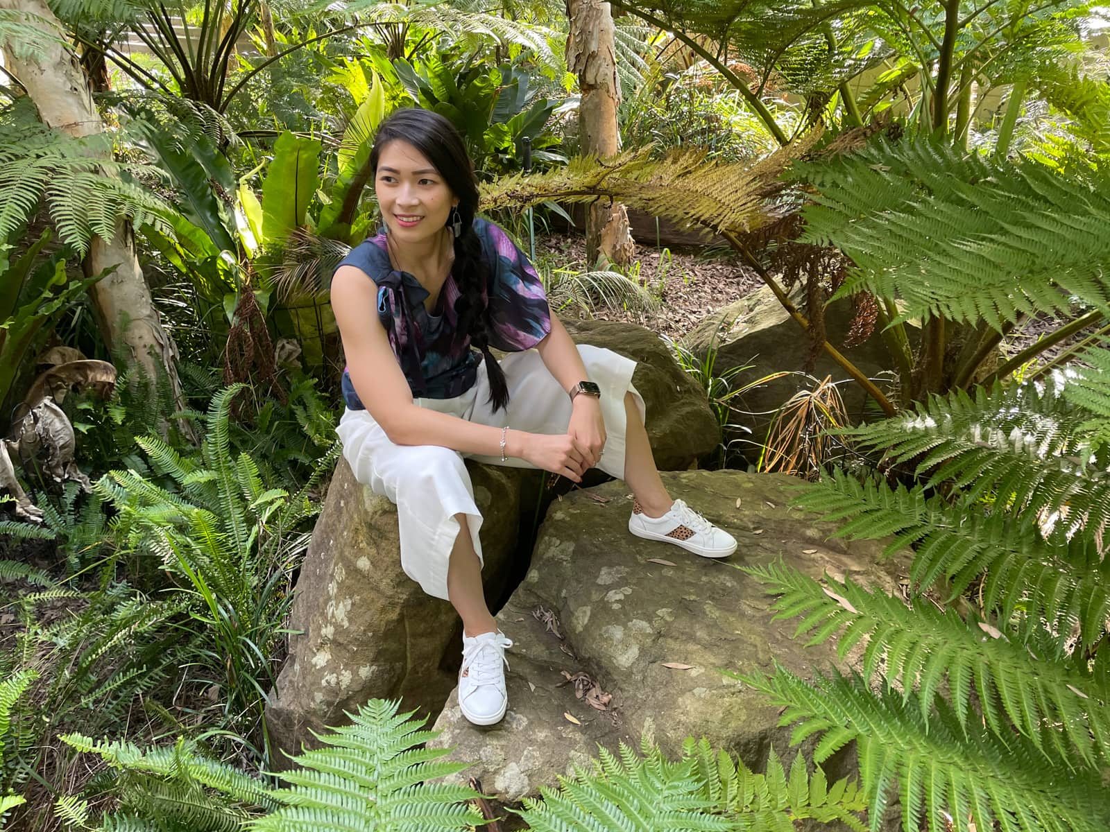 A woman with fair skin and long dark hair braided loosely in a side braid. She is wearing a dark top with a blue and purple floral pattern, white loose short pants, and white sneakers. She is sitting on a rock amongst some trees with fern-like fronds.